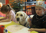 Chili examines crafts that 4- and 5-year-olds at Medina Weekday Preschool are making Tuesday, April 30, 2013. Teacher Staicey Scholtz takes Chili, a service dog in training, to the school tw …