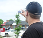 James Purdy, of Brunswick, snaps a photo of two Medina police cars observing Saturday afternoon's demonstration walk by open carry firearms supports along the North Court retail district. (D …