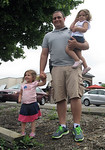 """Brett Pucillo, president of Ohio Carry, poses with his daughters, 3-year-old Aubree and 2-year-old Addison, at an """"open carry"""" firearm demonstration walk Saturday afternoon. Pucillo carried  …"""